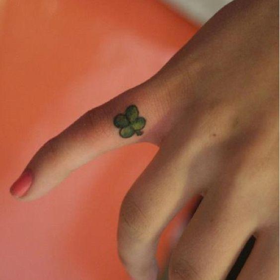mano de una mujer, con las uñas pintadas de rosa, en su dedo pequeño tatuaje de trebol