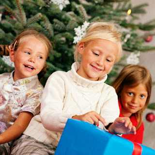 Photo of three children with a Christmas gift