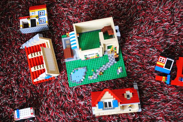 Lego city sets van bovenaf, een kapot huis, een politiewagen en een omgevallen ziekenhuis en brandweerstation.