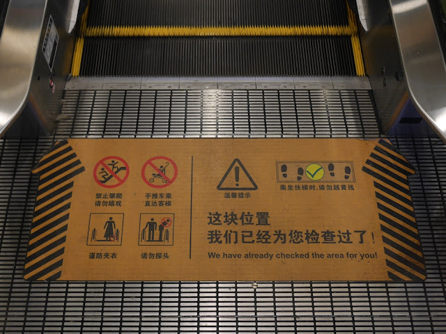 """sign on floor just after moving part of escalator with """"We have already checked this area for you!"""""""