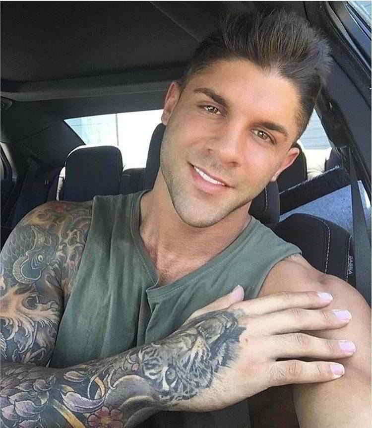 Imagen de un hombre con tatuajes de estilo japones, carpas koi