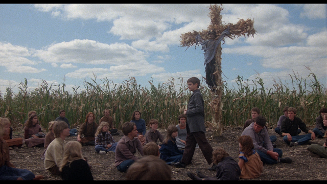 the children of the corn listen as their tiny master tells them what they already know