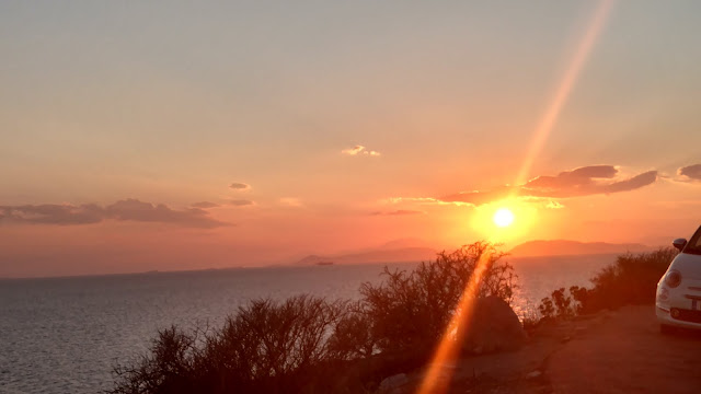 the sun sets over the Aegean Sea and Athens, Greece