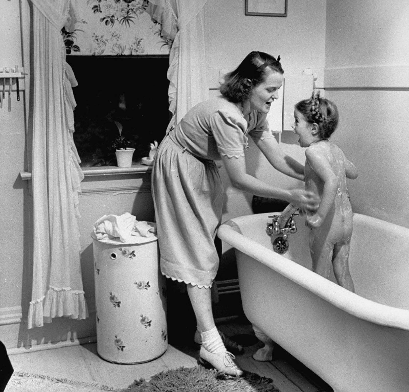 Jane bathing her daughter Pamela, 4, before dressing her for bed at night.