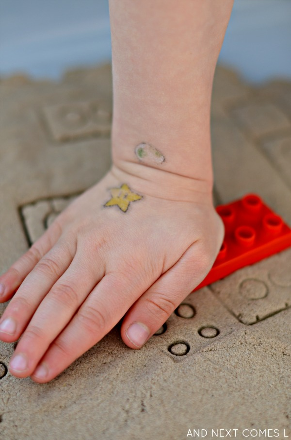 Stamping LEGO in kinetic sand - fine motor activity for kids from And Next Comes L