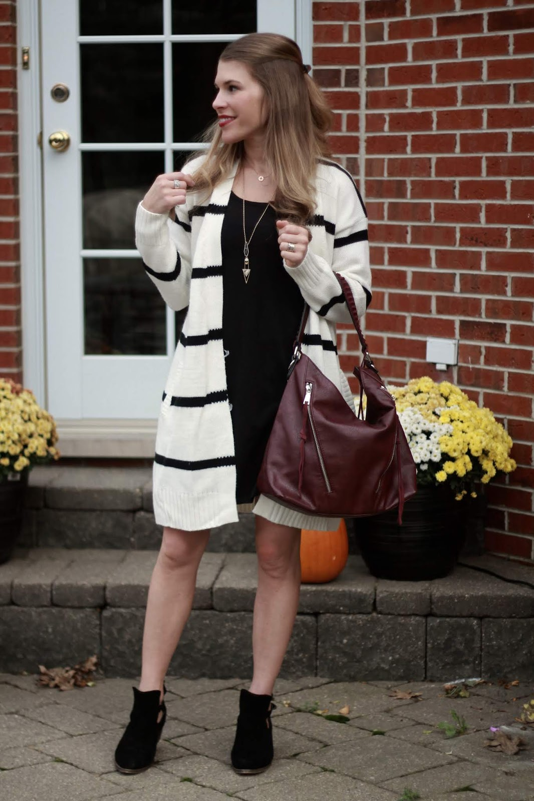 black dress, striped cardigan, black booties, burgundy bag