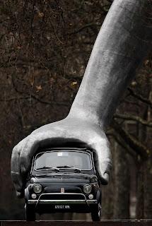 Mano gigante con un auto tamaño normal
