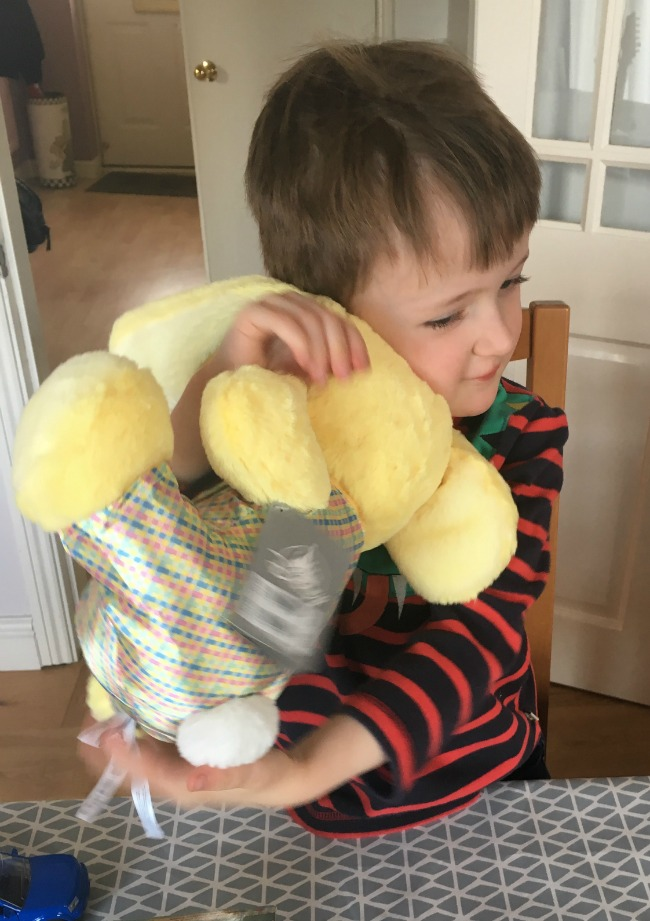 boy-cuddling-Disney-store-soft-toy-furry-yellow-with-rabbit-ears-face-not-visible