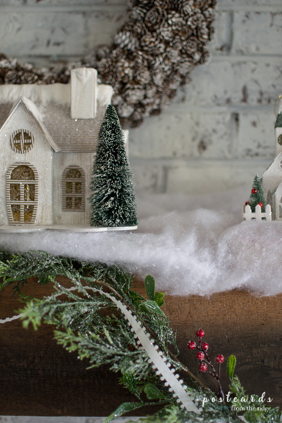 Snowy paper house with bottle brush tree on a farmhouse Christmas mantel