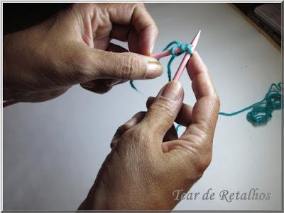 Foto mostrando a colocação do laço formado na agulha direita na a agulha esquerda. Técnica de montagem à inglesa da base de pontos do tricô