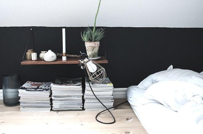 detalle del dormitorio con cama sin somier y pared blanca-negra