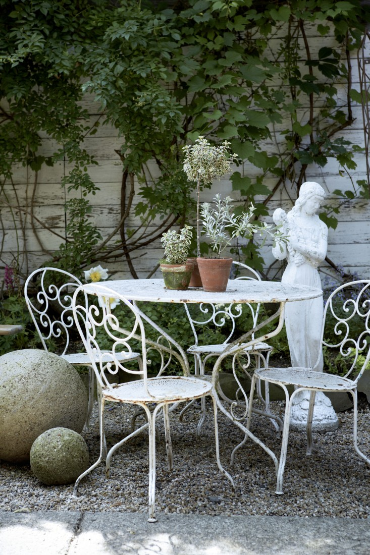 Charming white iron patio furniture in pea gravel courtyard garden on Hello Lovely Studio