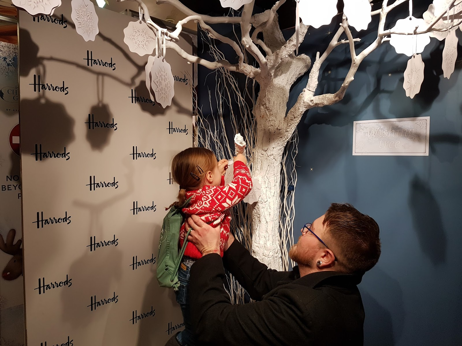 hanging a wish to a christmas wish tree at harrods christmas grotto 2016