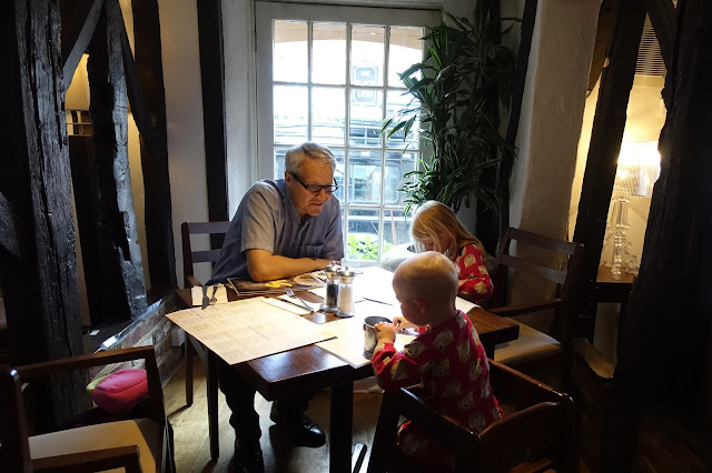 A Dad and 2 children sitting at a table in front of a window surrounded by wooden beams