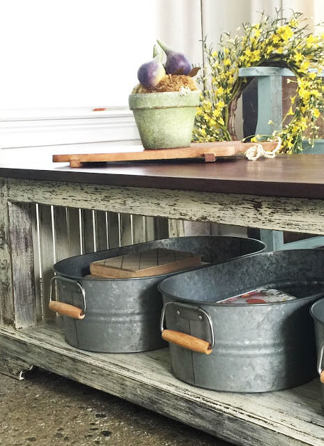 Two galvanized tubs with handles tucked under a table with books and magazines inside