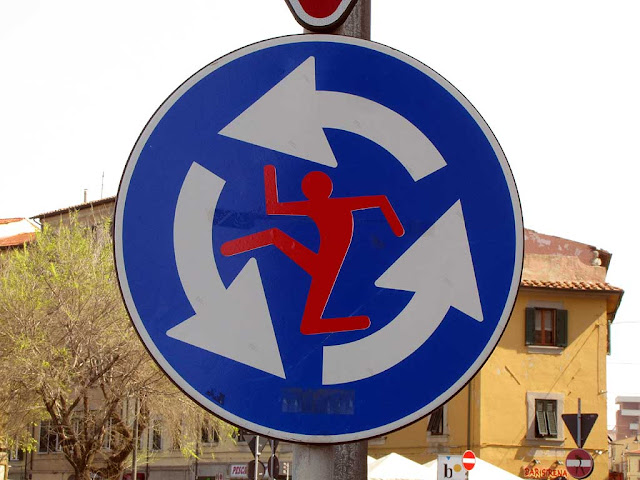 Roundabout sign with a running man inside, Clet Abraham, piazza Mazzini, Livorno