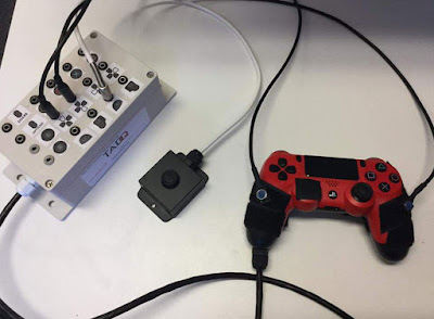 White switch interface box with 15 sockets, external stick and an adapted red PS4 controller with velcro.