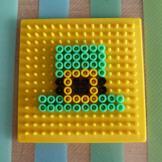 Yellow pegboard with green Leprechaun hat bead pattern