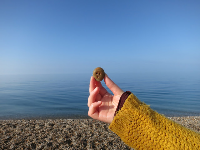 Pebble with face made by sea with pebbles in the foreground and the sea beyond.