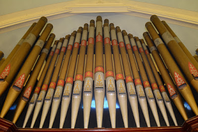 Close up of gold colored pipe organ pipes