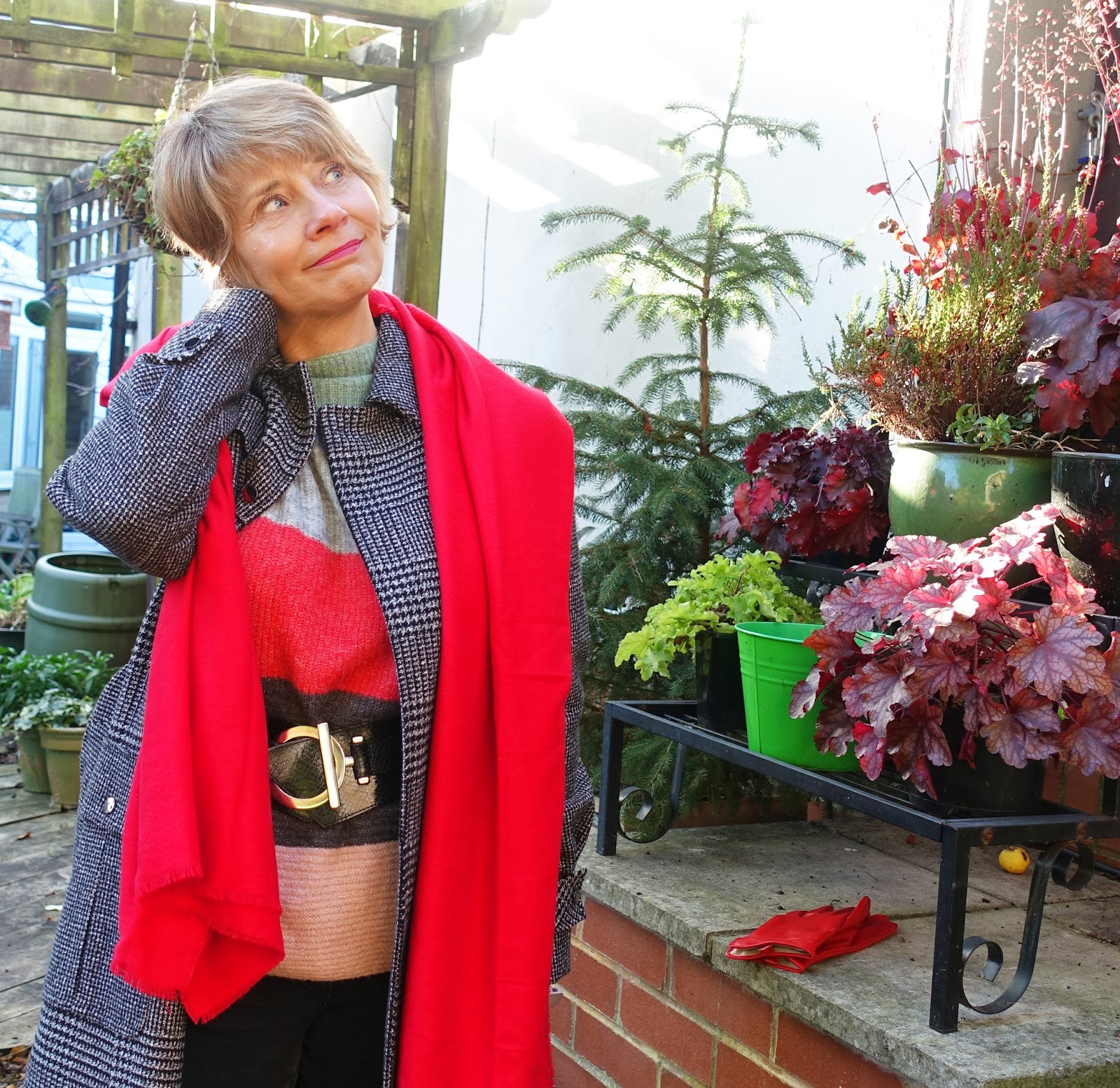 Image showing an over 50s woman in black and white check coat and red accessories for winter 2017 on a chilly day in the garden.
