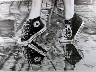 Fotografía en blanco y negro de las piernas de una chica joven a la que solo se le ven las zapatillas tipo Converse negras y blancas, caminando bajo la lluvia.