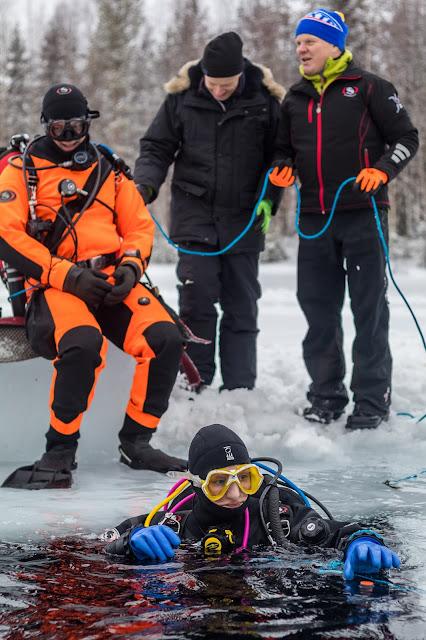 Sukeltaja avannossa, toinen istuu turvasukeltajana jäälohkareella, kaksi henkeä pitää kiinni sukeltajan narusta