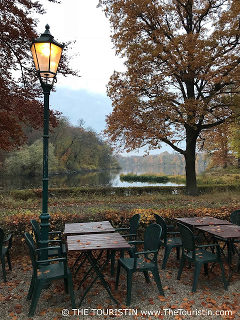 Deserted beer garden tables on a lake, next to a streetlight. Leaves scattered all over. Trees with colourful foliage create the background.