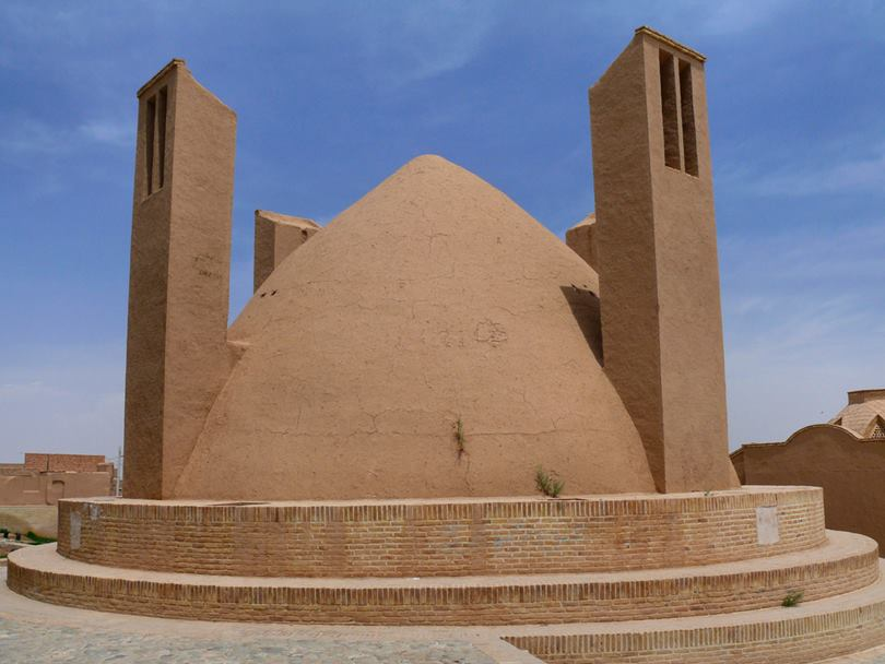 A badgir: typical iranian desert natural cooling system made with mud bricks and Adobe. It uses the air circulation between 2 towers passing through a dome refreshed by the flow of water into an underground channel named Qanat.