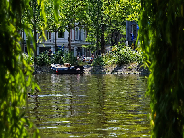 Boat on the river, taken from underneath a willow tree and overlooking the canal in Amsterdam.
