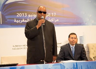 Stevie Wonder standing with a mic, addressing a conference