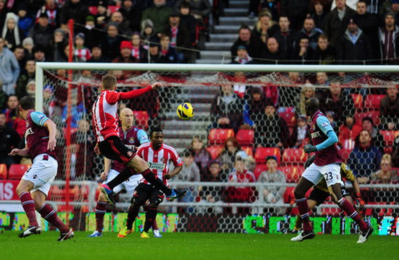 Sunderland player Sebastian Larsson shoots to score the first goal against West Ham