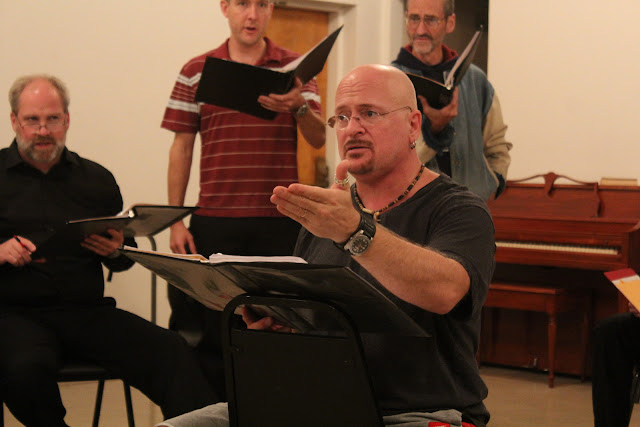Pierre Massie directs the Stairwell Carollers in rehearsal