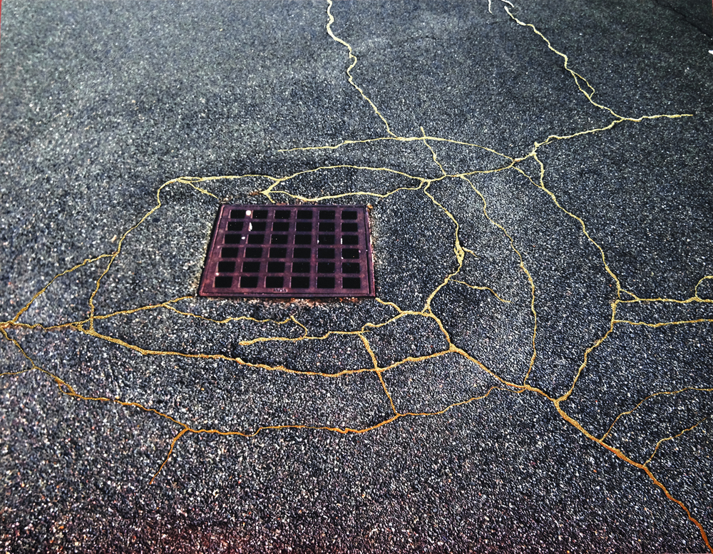 Ein Kanaldeckel auf einer gerissenen Straße, die Risse wurden mit Gold aufgefüllt und zeichnen so goldene Linien auf dem Bürgersteig