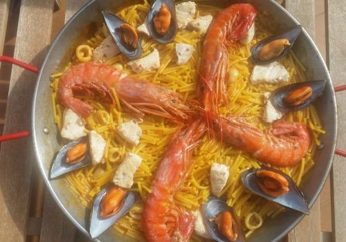 Una paella hecha con fideos, marisco y emperador