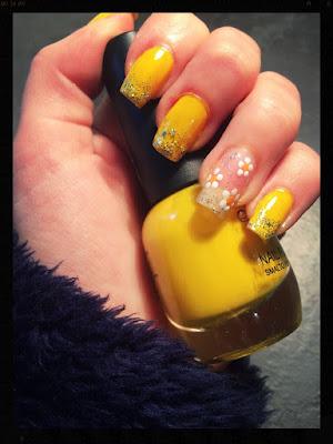 unghia gialla con la punta brillantinata e il fiore realizzata con il dotter