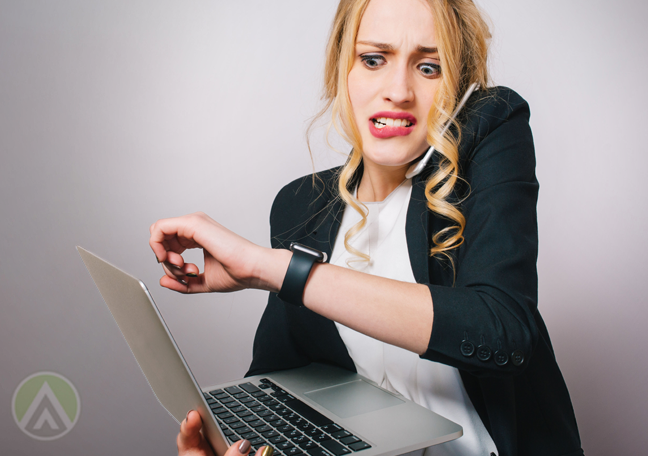 panicking woman holding laptop looking at wristwatch