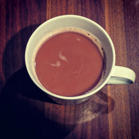 image of a mug of hot cocoa from above, sitting on my coffee table