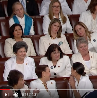 The Democratic Women — dressed in white to honor the 100th anniversary of women s right to vote — stand and cheer as Trump says just the right things to rouse them out of what I think was supposed to be grim disapproval.