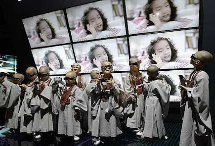 Shaven-headed young boys wearing 3-D glasses watch a 3-D TV