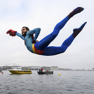 A swimmer dressed as Superman diving into Lake Geneva for the 78th Coupe de Noël