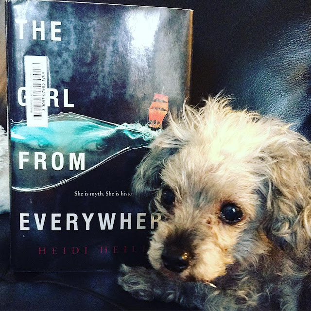 Murchie lies slightly in front of a hardcover copy of The Girl From Everywher. Its black cover features a black ship with red sails, poised atop a swirl of blue sea with a girl's eyes reflected in it.