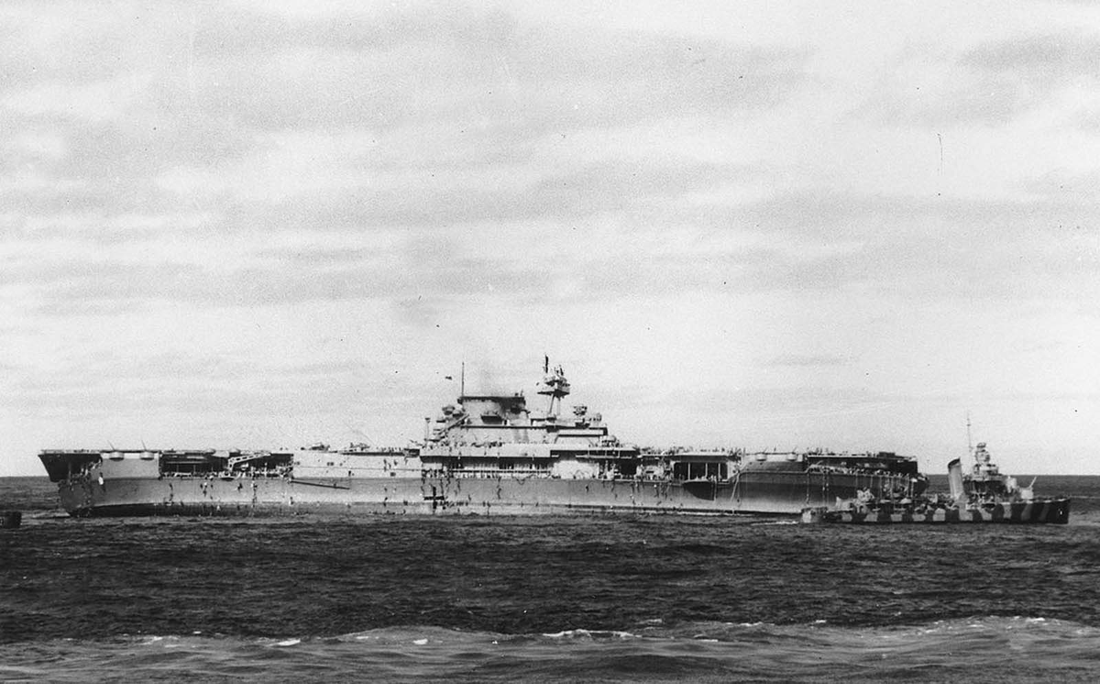 After Japanese bombers damaged the USS Yorktown, crewmen climb down ropes and ladders to small boats that transferred them to rescue ships, including the destroyer at right, on June 4, 1942 in the Pacific Ocean. Later, a salvage crew returned to the abandoned ship and as she made progress toward port, a torpedo from a Japanese submarine destroyed and sank the Yorktown.