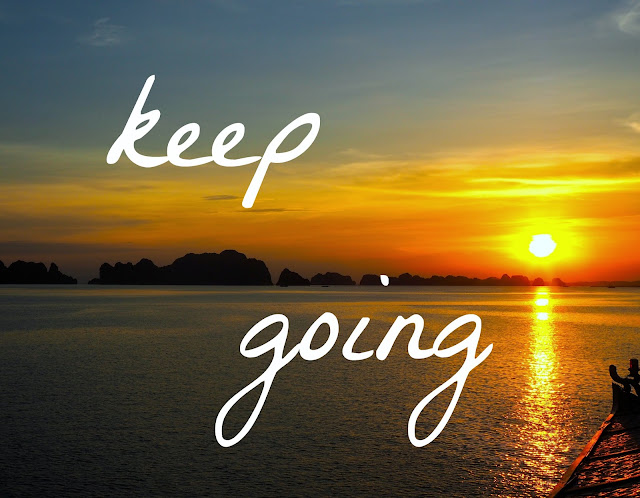 """Keep Going"" motivational text on ocean sunset background with boat, in Halong Bay"