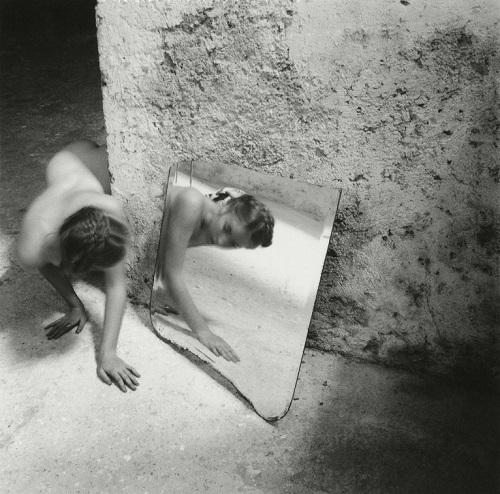 Foto cool: una joven gatea en una vieja habitación mientras se mira al espejo.