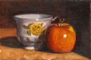 Oil painting of a white teacup with yellow rose decoration beside a red apple.