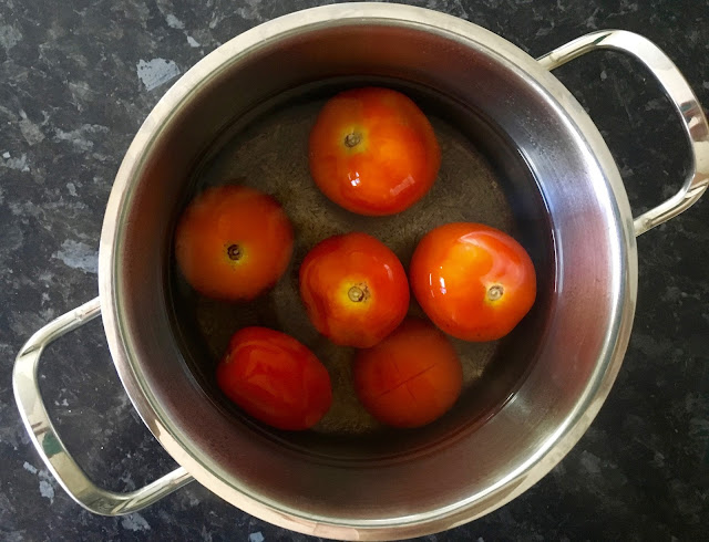 Peeling fresh tomatoes in hot water