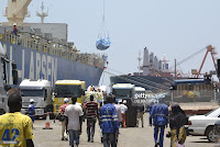 Trucks loaded with rice are parked at a shipping dock of the Autonomous Port of Conakry, on April 13, 2016. The Bollore group headquarters, which houses Bollore Africa Logostics, was searched on April 8, 2016 as part of an investigation into the conditions of how concessions were granted in the use of the harbours of Conakry (Guinea) and Lome (Togo), it was announced on April 12, 2016.  (Credit: / AFP / CELLOU) Click to Enlarge.