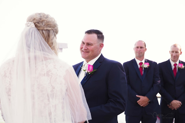 groom during vows at new baltimore waterfront wedding