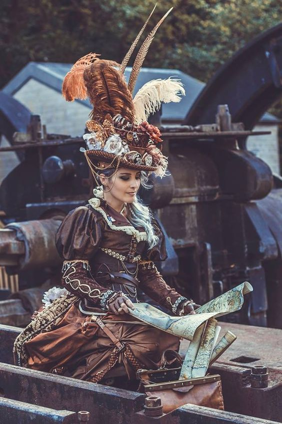 woman dressed in steampunk costume (brown, orange, rust, copper) with giant feather hat, boots, skirt, corset